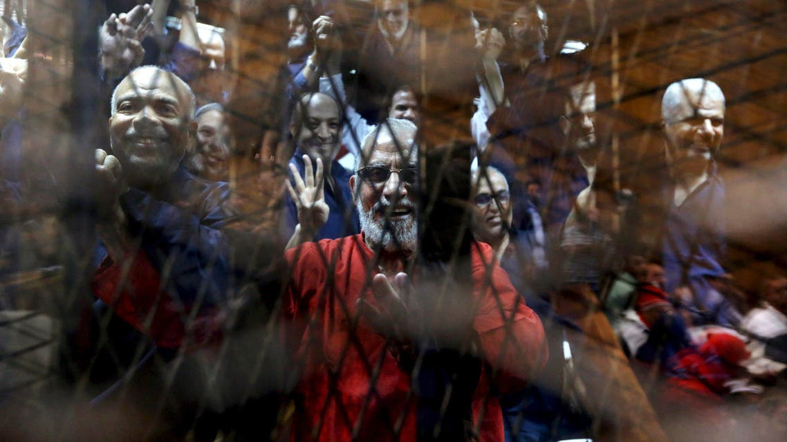 Muslim Brotherhood's Supreme Guide Mohamed Badie (C) waves with the Rabaa sign, symbolizing support for the Muslim Brotherhood, with other brotherhood members at a court on the outskirts of Cairo, Egypt in this May 16, 2015 file photo. To match Special Report EGYPT-LAWYERS/ REUTERS/Mohamed Abd El Ghany/Files