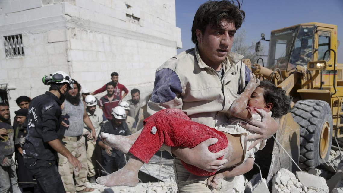 Civil defense member carries an injured girl that survived from under debris at a site hit by what activists said was an airstrike by forces loyal to Syria's President Bashar al-Assad in the southern countryside of Idlib. (File: Reuters)
