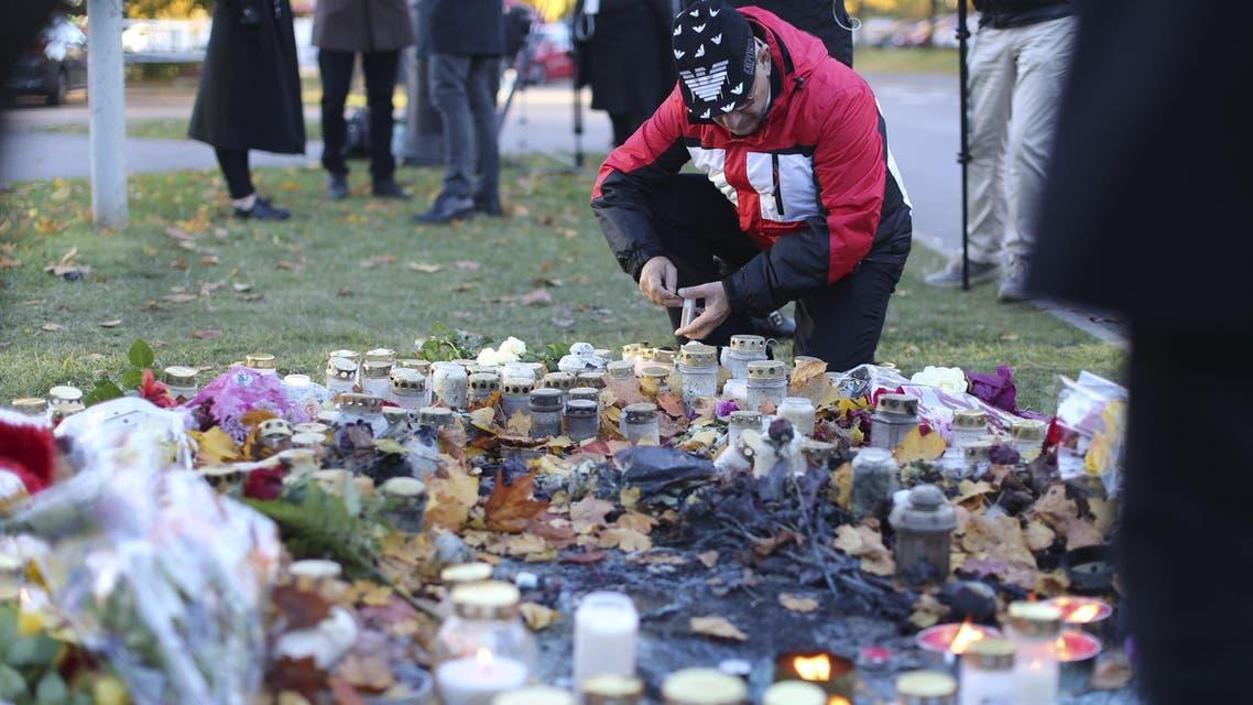 A man lights a candle outside Kronan school in Trollhattan, Sweden October 23, 2015.