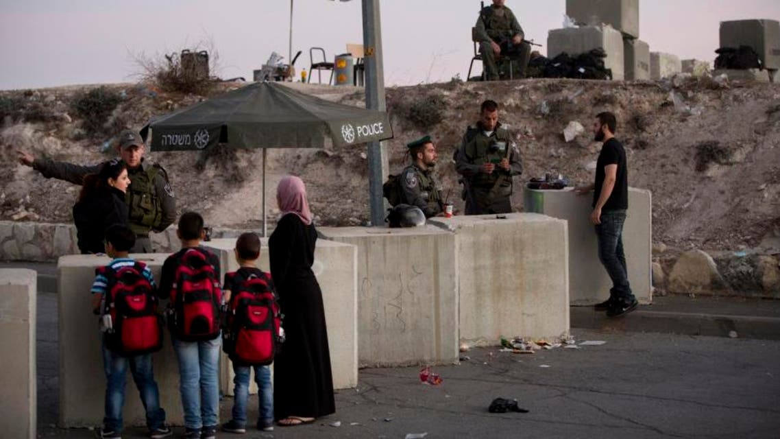 Israeli border police check Palestinian's identification cards at a checkpoint as they exit the Arab neighborhood of Issawiyeh in occupied Jerusalem. AP)