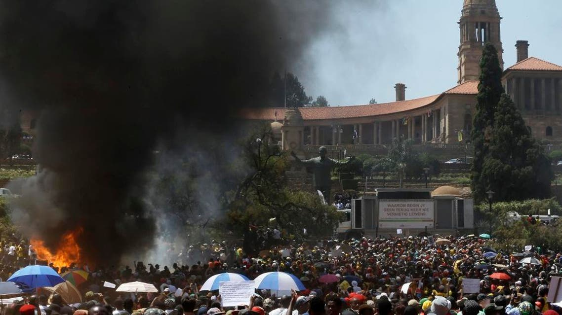 Students burn portable toilets during their protest against university tuition hikes outside the union building in Pretoria, South Africa, Friday, Oct. 23, 2015. AP