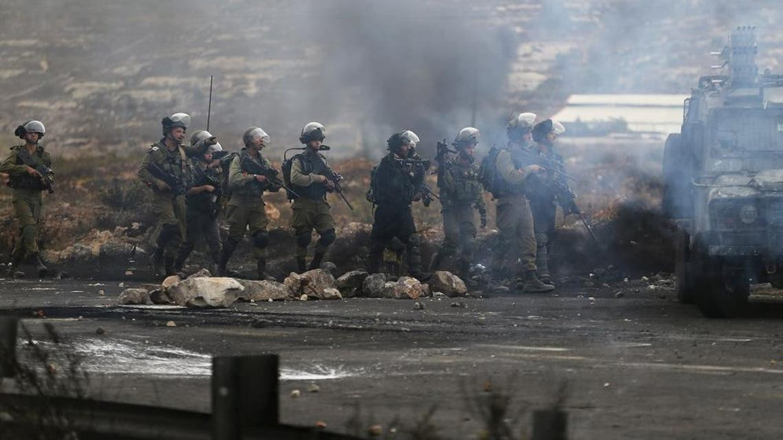 Israeli soldiers and policemen take position during clashes with Palestinians near the Jewish settlement of Bet El, near the West Bank city of Ramallah. (Reuters)