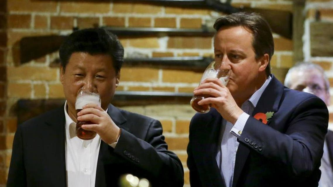Britain's Prime Minister David Cameron drinks beer with Chinese President Xi Jinping at a pub in Princess Risborough. (Reuters)