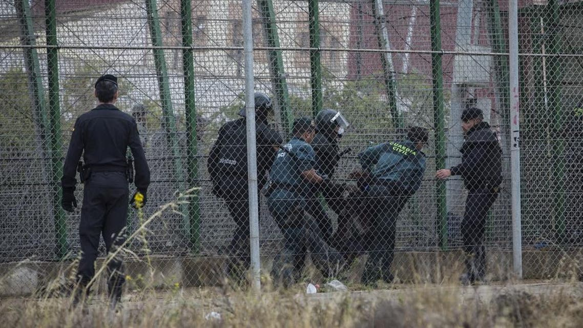 Sub-Saharan migrants are sent back to the Moroccan side escorted by Spanish Guardia Civil officers after climbing a metallic fence that divides Morocco and the Spanish enclave of Melilla. (AP)