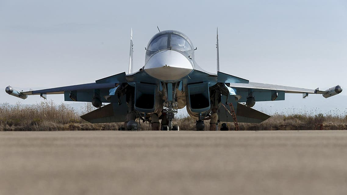 Russian ground staff members work on a Sukhoi Su-34 fighter jet at the Hmeymim air base near Latakia, Syria. (Reuters)