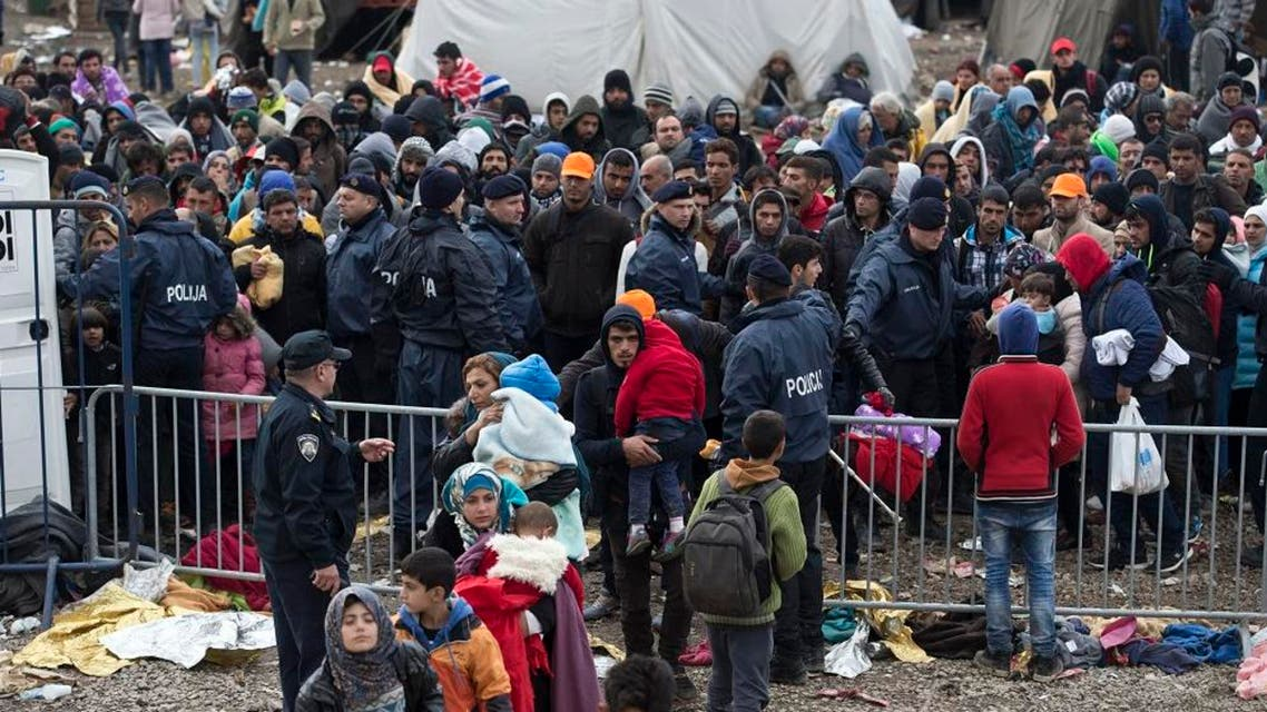 People wait to clear a police line at a registration center for migrants and refugees in Opatovac, Croatia, Wednesday, Oct. 21, 2015. Croatia, Serbia and Slovenia have struggled to cope with the relentless flow of migrants traveling through the Balkans, their journey made more difficult since Hungary erected fences protected by razor wire, police and soldiers on its southern borders, forcing migrants to find new routes west. (AP Photo/Marko Drobnjakovic)