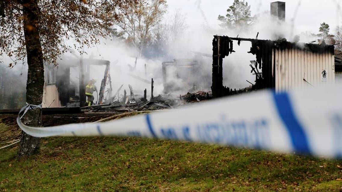 A firefighter works to extinguish a fire that broke out early in the morning at an accommodation for asylum seekers near Munkedal in Sweden, Tuesday, Oct. 20, 2015. Swedish police say they were investigating a case of suspected arson at an asylum center in southwestern Sweden where over a dozen people were safely evacuated from the burning building in the early hours of Tuesday. (Adam Ihse /TT News Agency via AP)
