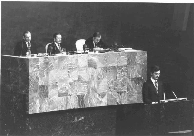 Prince Saud Al-Faisal, Minister for Foreign Affairs of Saudi Arabia, is seen here addressing the Assembly, at the presidential rostrum, (L-R) Secretary General Kurt Waldheim; Assembly President Gaston Thorn (Luxembourg); and Bradford Morse, Under Secretary General for Political and General Assembly Affairs in September 1975