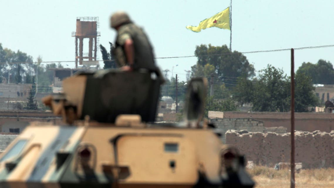 a Turkish soldier on an armoured personnel carrier watches as in the background a flag of the Kurdish People's Protection Units, or YPG, is raised over the city of Tal Abyad AP