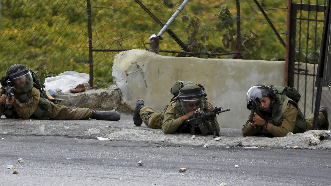 "Israeli soldiers take position during clashes with Palestinian protesters in the West Bank city of Hebron October 23, 2015. Palestinian factions called for mass rallies against Israel in the occupied West Bank and East Jerusalem in a ""day of rage"" on Friday, as world and regional powers pressed on with talks to try to end more than three weeks of bloodshed. REUTERS/Mussa Qawasma"