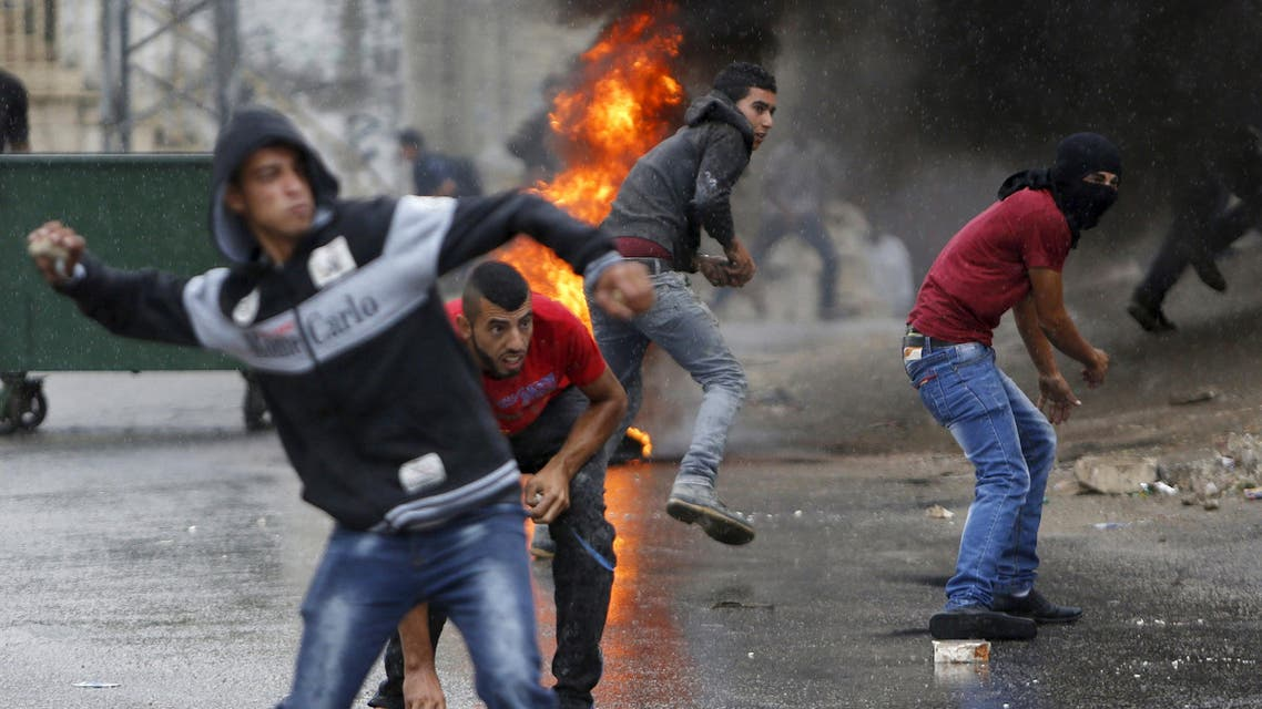 Palestinians hurl stones at Israeli troops during clashes in the West Bank village of Si'eer north of the West Bank city of Hebron October 25, 2015. (Reuters)