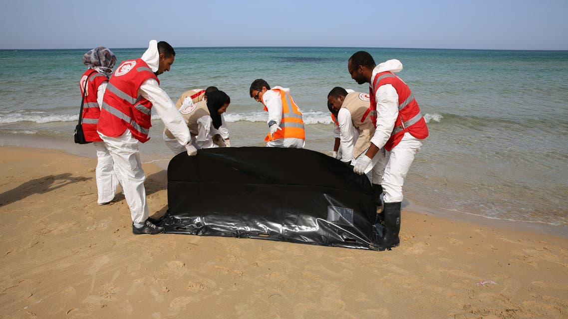 Red Crescent workers prepare to carry the lifeless body of a migrant, off the shore of Gasr Garabulli, in the eastern city of Tripoli, Libya, Wednesday, Oct. 21, 2015. Red Crescent collected the bodies of six people including an infant. (AP Photo/Mohamed Ben Khalifa)