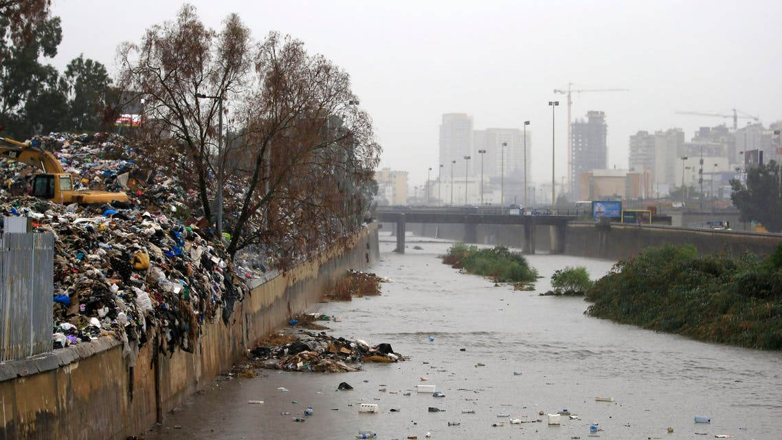 A pile of garbage, left, lies on the bank as trash floats on the Beirut River, in Karantina, east Beirut, Lebanon, Sunday, Oct. 25, 2015. Early heavy showers Sunday in Lebanon's capital Beirut compounded the city's trash problem, as trash pilling in the streets and along river banks started flowing with the rain water, raising a public health scare. The Beirut river, where garbage has piled on the banks, was also flooded with trash and activists volunteered to clean it, reinvigorating the anti-government activist campaign. (AP Photo/Hassan Ammar)