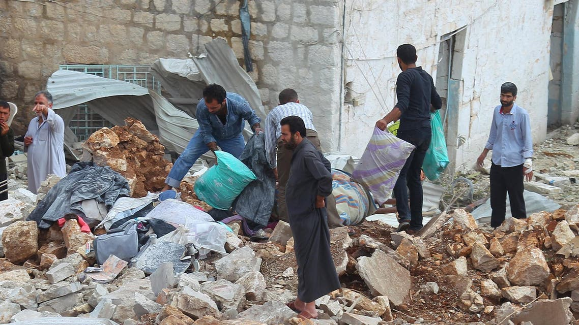 Civilians carry belongings recovered from a site hit by what residents said were airstrikes carried out by the Russian air force in the town of Darat Izza in Aleppo's countryside October 7, 2015.  (Reuters)