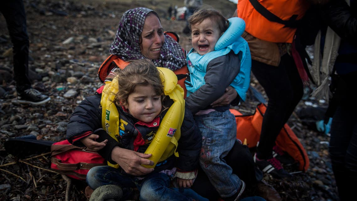 A woman holds two children on a beach after arriving on a dinghy from a Turkish coast to the northeastern Greek island of Lesbos, Sunday, Oct. 25, 2015.