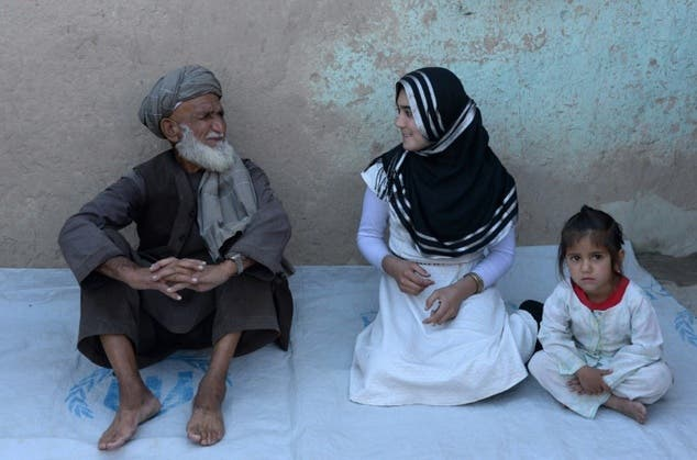 Aziza Rahimzada, (C), who has been nominated for the International Children's Peace Prize, speaks with her father Jandad Rahimzada at a refugee camp in Kabul