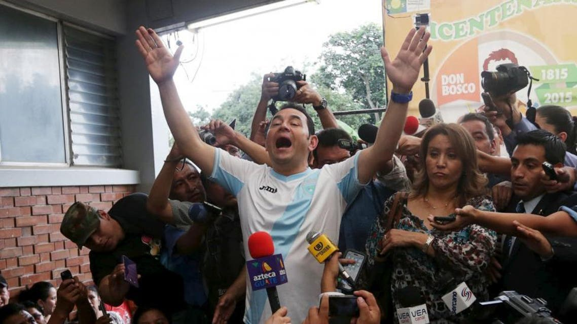 Jimmy Morales (C), presidential candidate for the National Convergence Front party (FCN), gestures while addressing the media next to his wife Gilda Marroquin (R) after casting his vote at a polling station in Guatemala City. (Reuters)