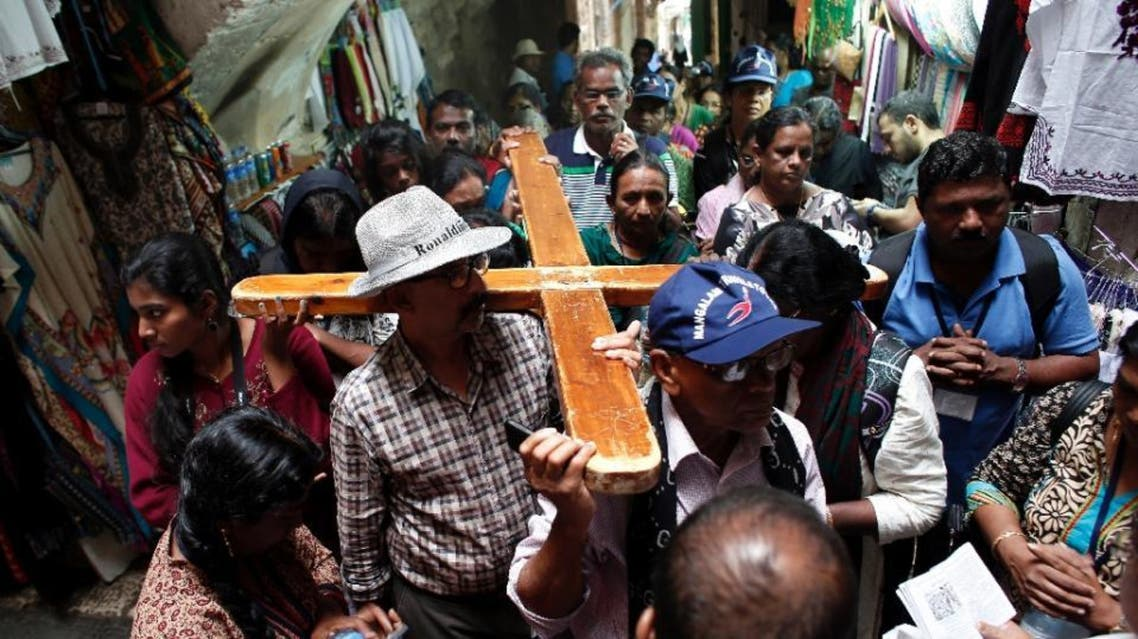 A small group of Christian pilgrims carry a cross in the Via Dolorosa street deserted by tourists in the Jerusalem's Old City, on October 23, 2015 (AFP)