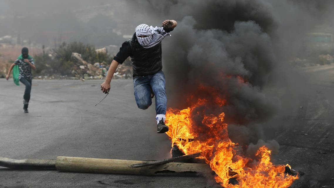 A Palestinian protester jumps past a burning tyre during clashes with Israeli troops during clashes near the Jewish settlement of Bet El, near the West Bank city of Ramallah October 27, 2015. REUTERS