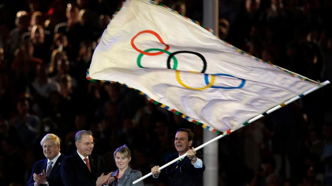 Rio de Janeiro mayor Eduardo Paes waves the olympic flag next to Jacques Rogge and London Mayor Boris Johnson. (File photo: AP)