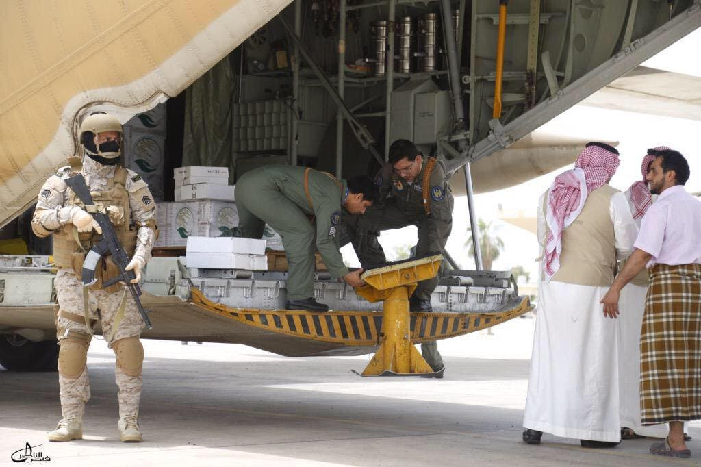 A Saudi soldier stands guard as servicemen on a Saudi military cargo plane prepare to unload aid at the international airport of Yemen's southern port city of Aden. (Reuters)