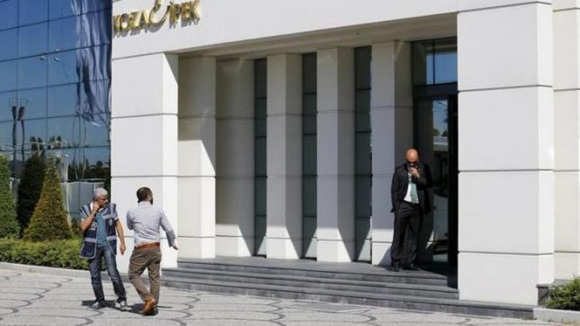 Two plainclothes police officers leave an office of Koza Ipek Group in Ankara, Turkey, September 1, 2015, as a company official stands at the entrance during a police raid. (Reuters)