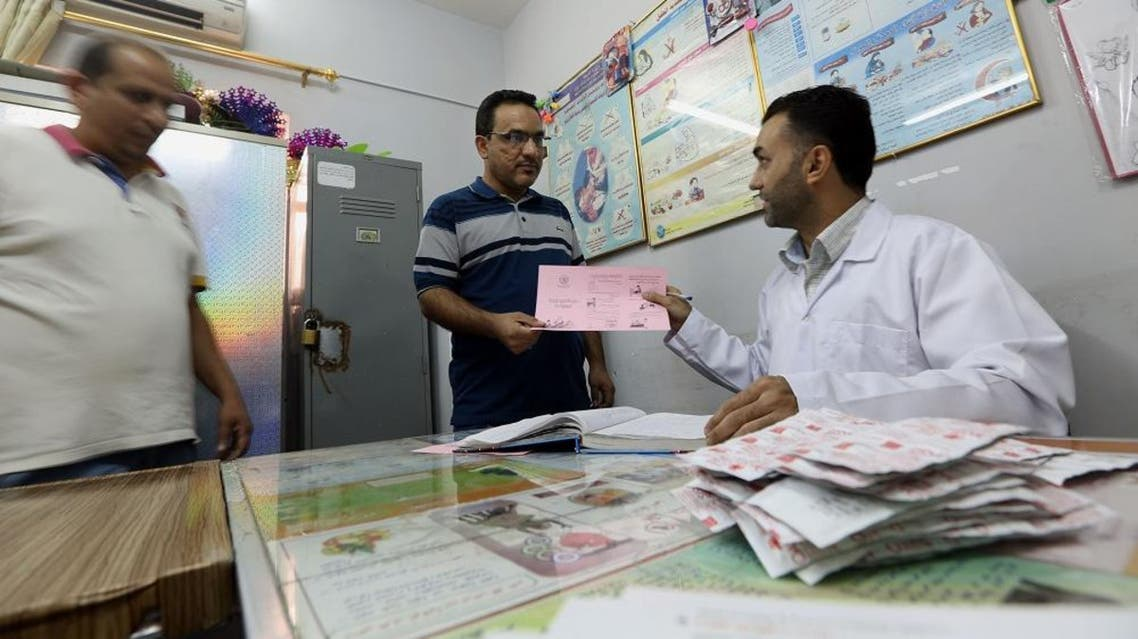 In this Tuesday, Sept. 22, 2015 photo, a doctor distributes cholera prevention guidance to citizens and government employees to avoid cholera in a cholera treatment clinic at the Medical City in Baghdad, Iraq. A cholera outbreak is the latest enemy plaguing the Iraq's government amid a growing humanitarian crisis in the face of threat posed by the Islamic State group. At least 54 cases have been confirmed in Baghdad, as well as in the southern provinces of Najaf, Diwaniyah, Babil and Samawah, Health Ministry spokesman Rifaq al-Araji told The Associated Press on Tuesday. (AP Photo/Hadi Mizban)