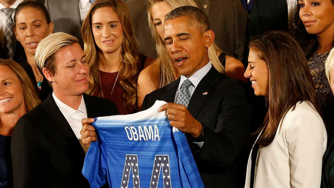 President Barack Obama holds an honorary team jersey while talking with Team USA forward Abby Wambach and midfielder Carli Lloyd. (Reuters)