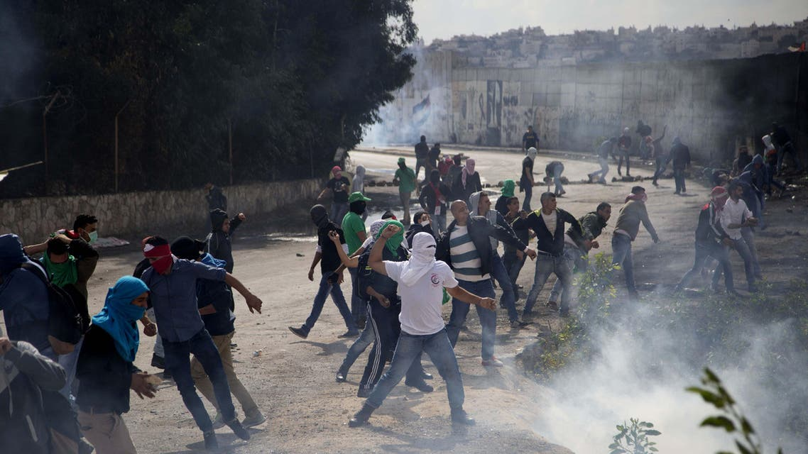 Palestinian students hurl stones at Israeli troops over the separation barrier during clashes following a protest near the Al-Quds University in the West Bank village of Abu Dis, near Jerusalem, Wednesday, Oct. 28, 2015. (APP)