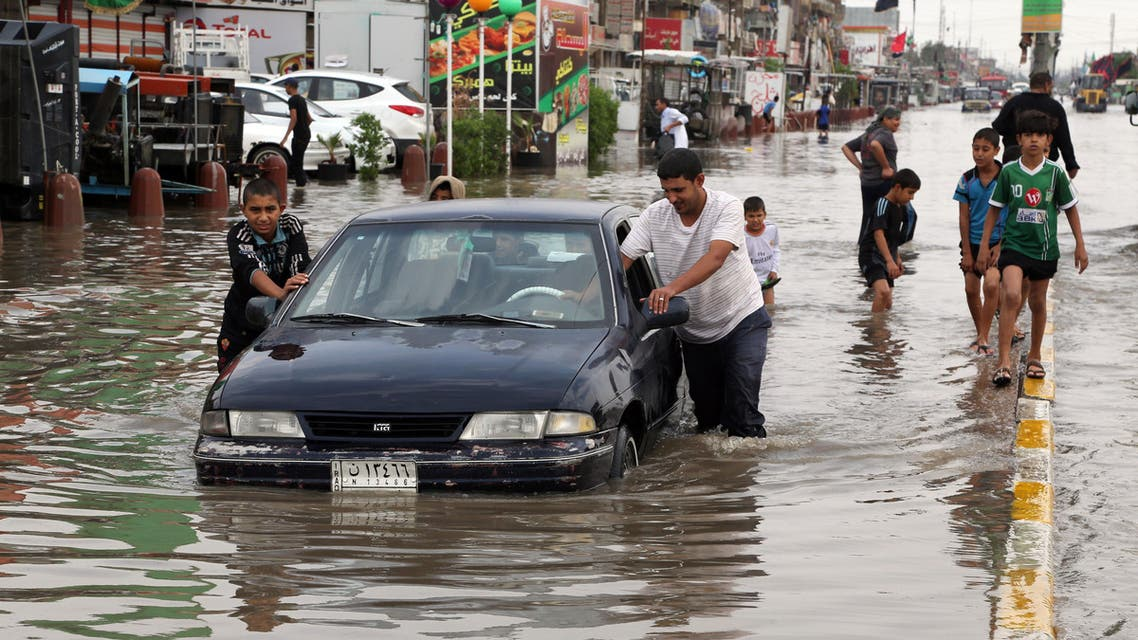 AP - Iraqis push a car, submerged in water, as others make their way through a flooded street after heavy rain fell in Baghdad, Iraq, Thursday, Oct. 29, 2015.