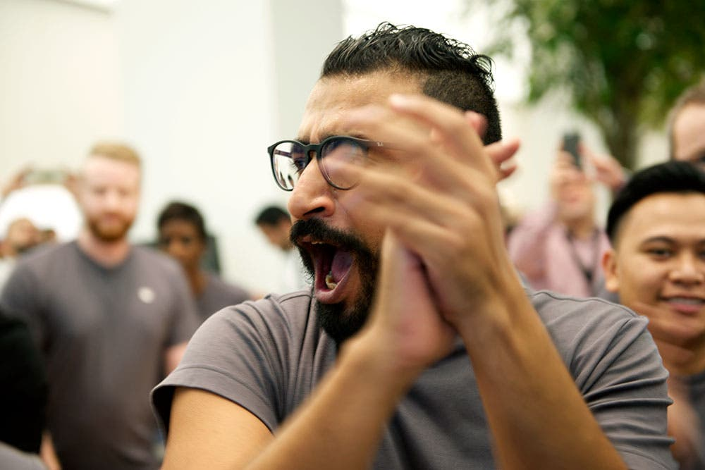 A member of staff claps and cheers as customers arrive at the Dubai Apple Store opening (Photo: Peter Harrison)