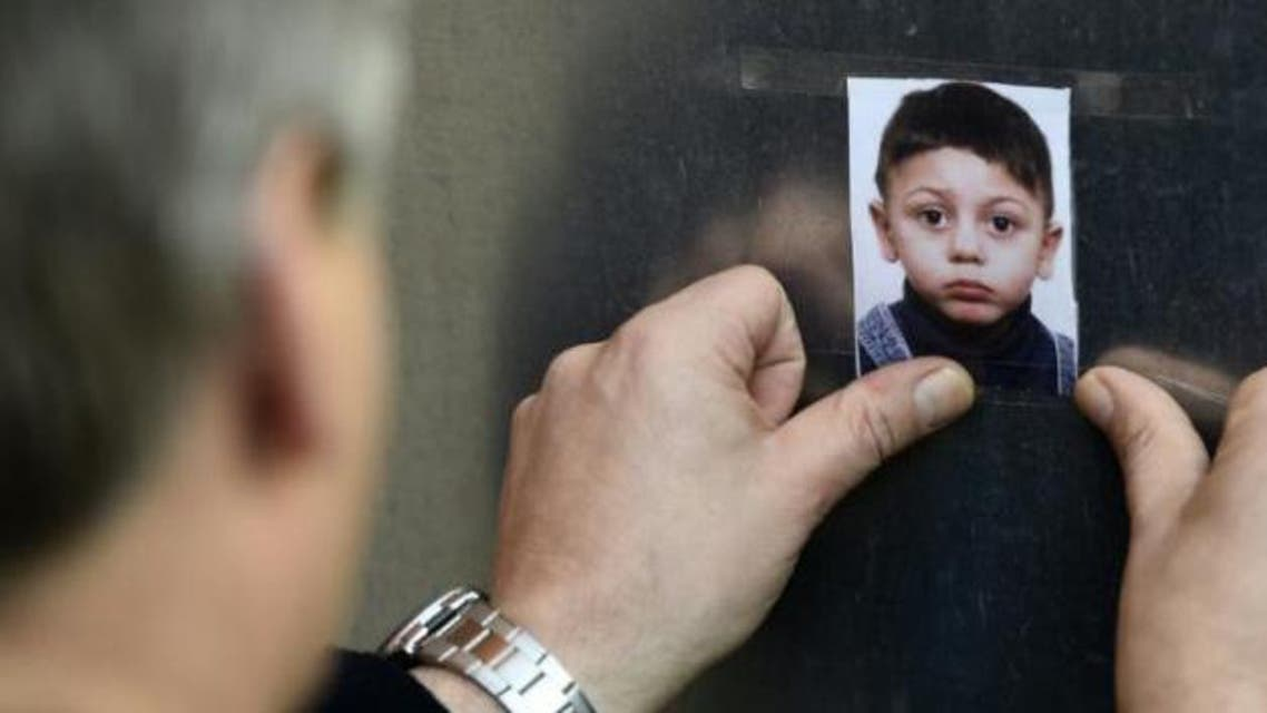 AFP/AFP - A man sticks a photo of missing Bosnian boy Mohamed on a wall at the State Office of Health and Social Affairs in Berlin on October 29, 2015 (AFP)