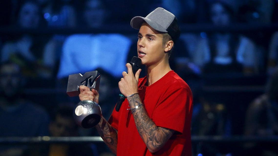 """Canadian singer Bieber holds the """"Best Collaboration"""" award during the MTV EMA awards at the Assago forum in Milan. (Reuters)"""