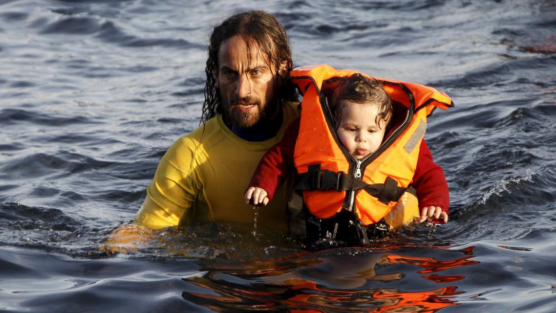 A volunteer lifeguard carries a baby as a half-sunken catamaran carrying around 150 refugees, most of them Syrians, arrives after crossing part of the Aegean sea from Turkey on the Greek island of Lesbos, October 30, 2015. There were no casaulties amongst the refugees who were travelling on the catamaran, according to a Reuters witness. The death toll from drownings at sea has mounted recently as weather in the Aegean has taken a turn for the worse, turning wind-whipped sea corridors into deadly passages for thousands of refugees crossing from Turkey to Greece. REUTERS/Giorgos Moutafis