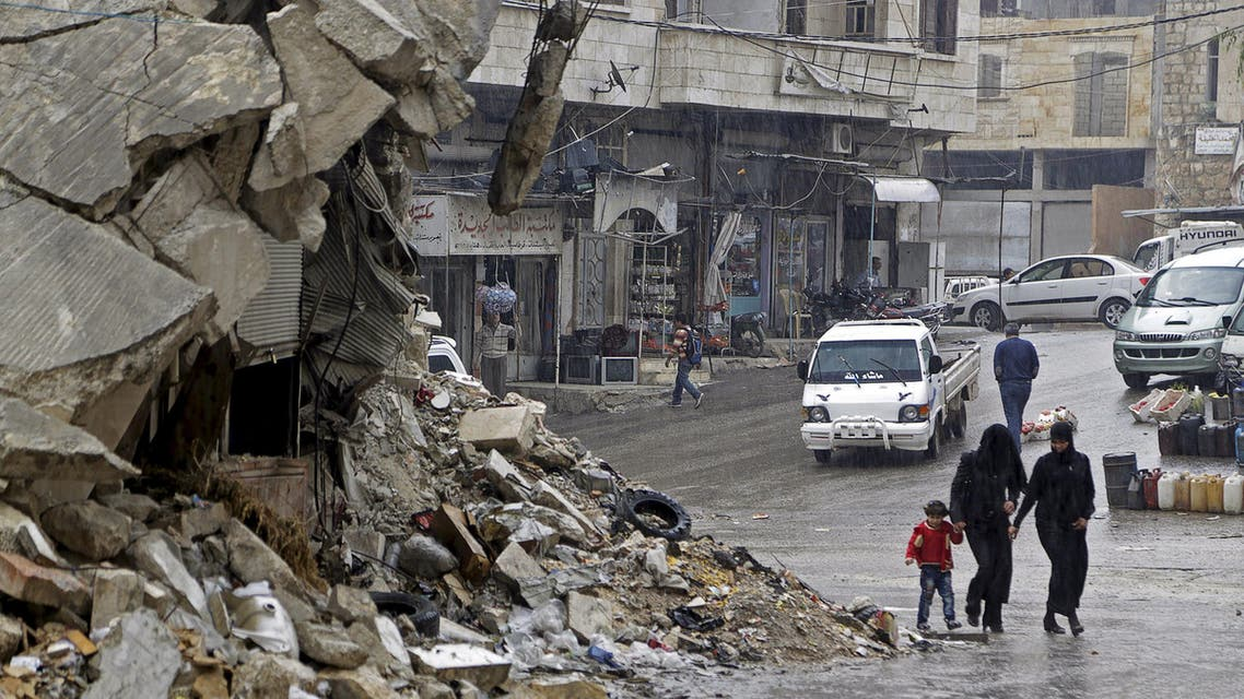 Civilians walk in the rain past a damaged building in the rebel-controlled area of Maaret al-Numan town in Idlib province, Syria October 28, 2015. (Reuters)