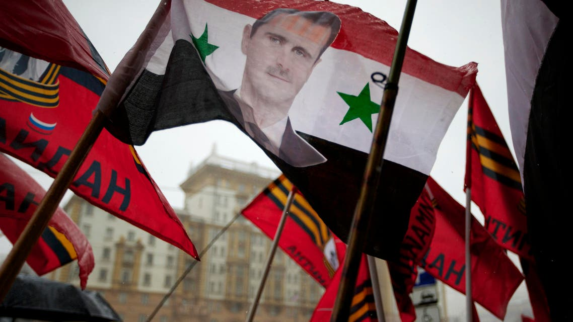 Pro-Kremlin youths hold a Syrian flag bearing a portrait of Syrian President Bashar al-Assad during a picket in protest against American policy in front of the U.S. Embassy in Moscow, Russia, Friday, April 3, 2015.  (AP)
