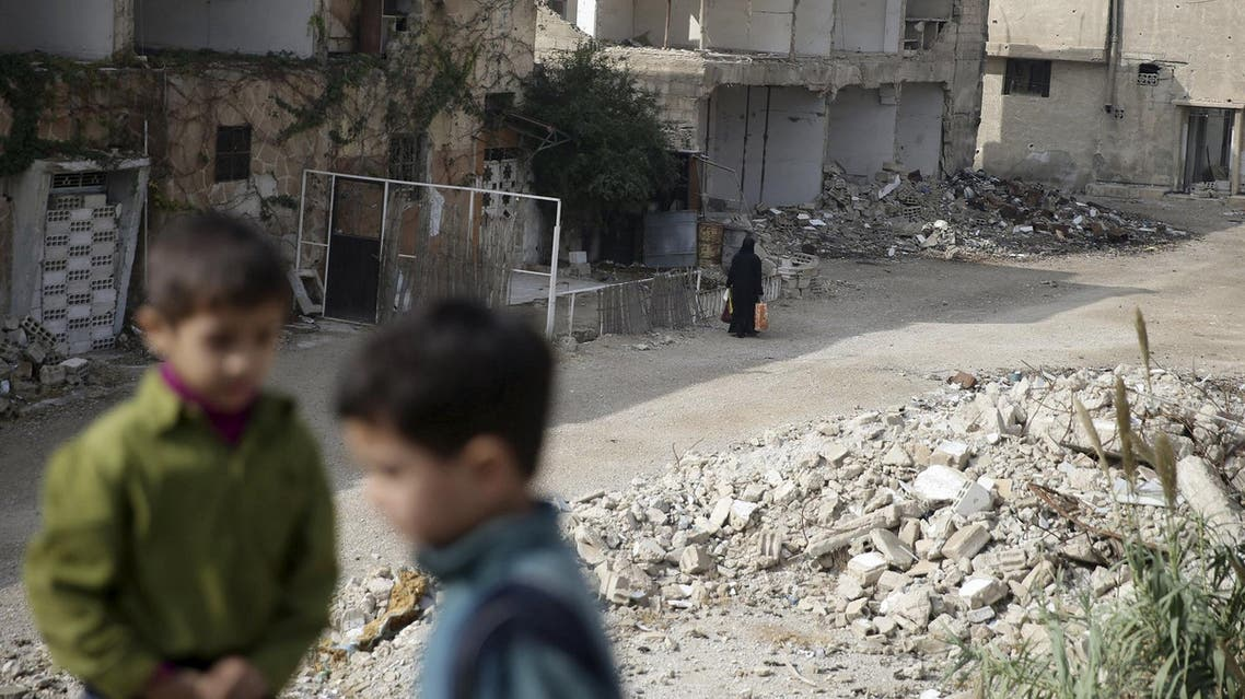 A woman walks near damaged buildings in the town of Douma. (File photo: Reuters)