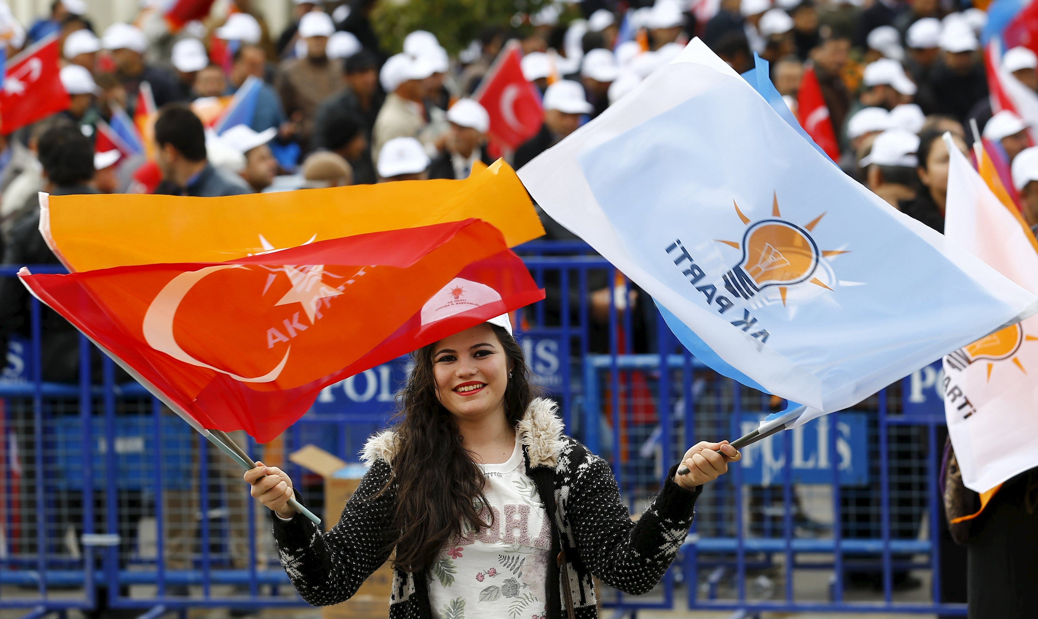 A supporter of the ruling AK Party waves national and party flags during an election rally in Ankara, Turkey, October 31, 2015.