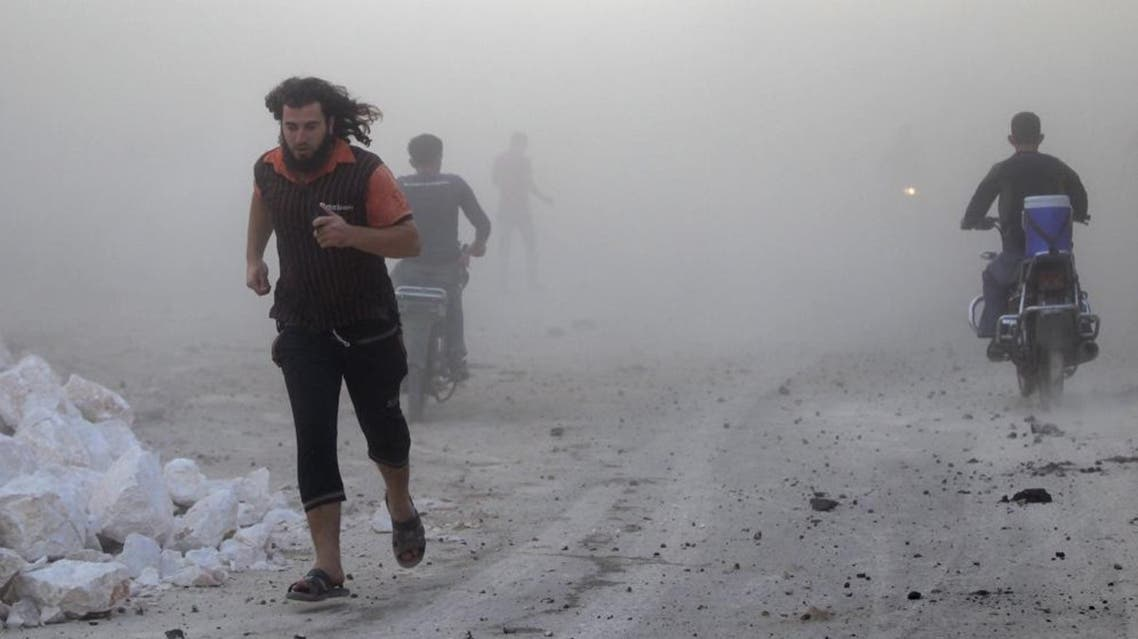 Residents run though dust in a site damaged by what activists said were airstrikes carried out by the Russian air force in the rebel-controlled area of Maaret al-Numan town in Idlib province. (File: Reuters)
