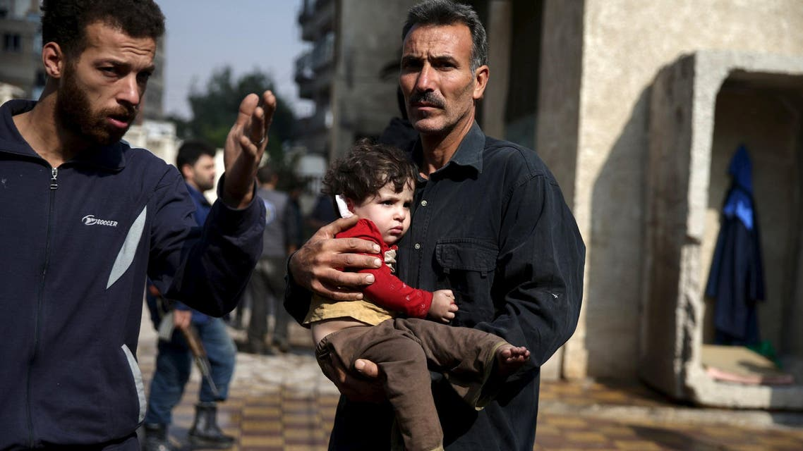 A man carries an injured child as another man gestures at a site hit by missiles fired by Syrian government forces on a busy marketplace in the Douma neighborhood of Damascus. (File: Reuters)
