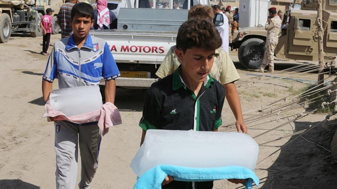 Internally displaced Iraqis carry ice at a camp near the Bzebiz bridge, 40 miles (65 kilometers) west of Baghdad, Iraq, Friday, Sept. 25, 2015. ap