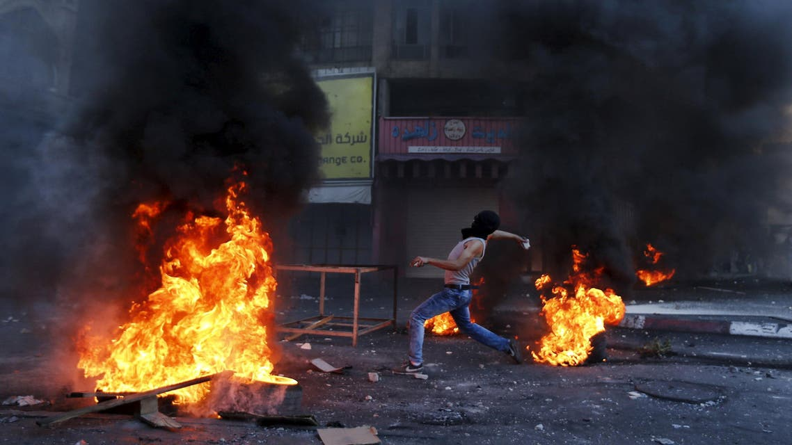 Palestinian protester hurl stones at Israeli troops during clashes in the West Bank city of Hebron. (Reuters)