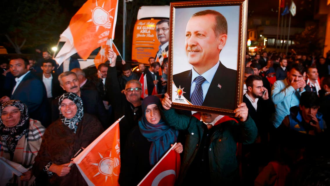 People wave flags and hold a portrait of Turkish President Tayyip Erdogan outside the AK Party headquarters in Istanbul, Turkey November 1, 2015. T