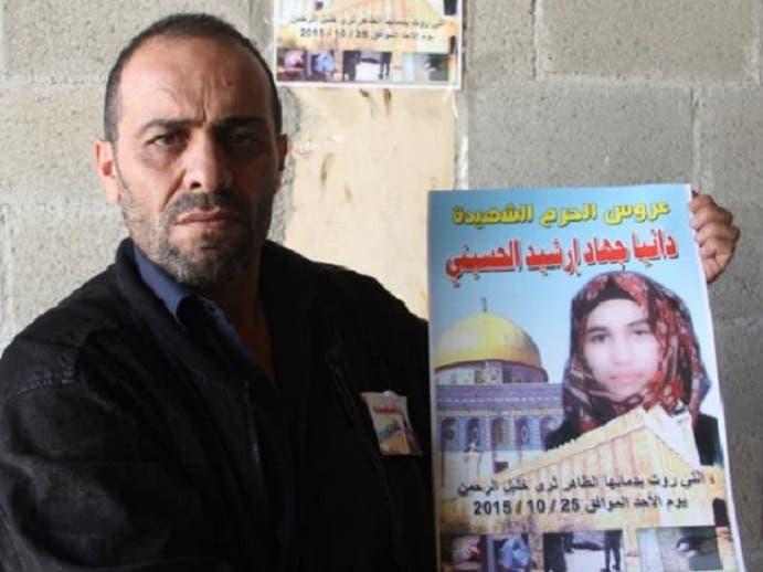 جهاد أرشيد يحمل صورة ابنته دانيا