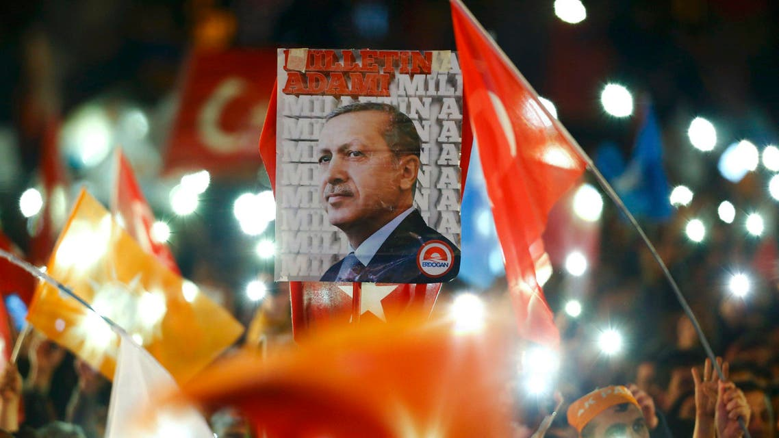 People wave flags and hold a portrait of Turkish President Tayyip Erdogan as they wait for the arrival of Prime Minister Ahmet Davutoglu in Ankara, Turkey November 2, 2015.