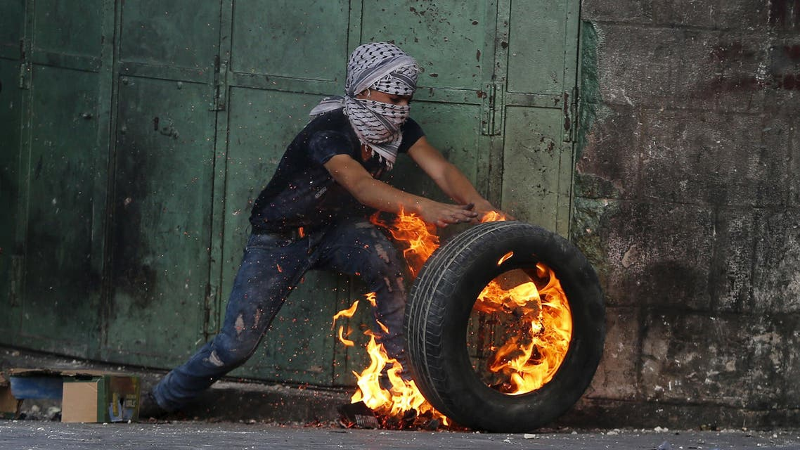 A young Palestinian protester pushes a burning tyre during clashes with Israeli troops in the West Bank city of Hebron October 31, 2015. Israeli security forces shot and killed a Palestinian who ran at them with a knife in the occupied West Bank on Saturday, police said, as a month-long wave of violence showed no signs of abating. REUTERS/Ammar Awad