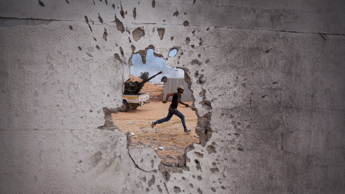 A Libyan revolutionary fighter runs for cover while attacking pro-Gadhafi forces in Sirte, Libya, Friday, Oct. 7, 2011. (AP)