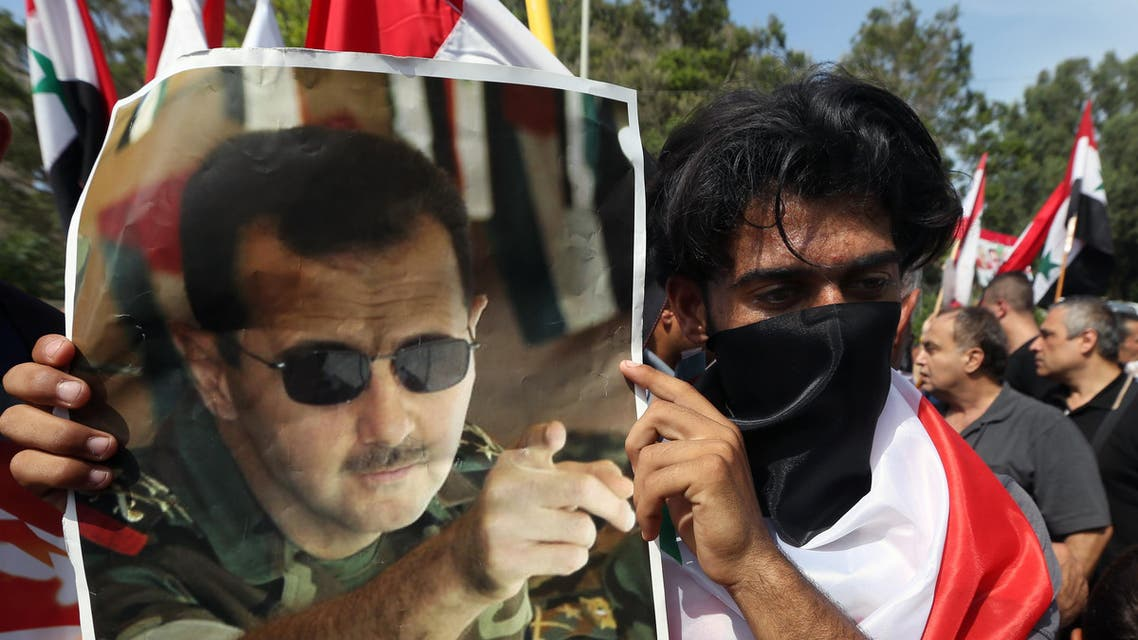 A Syrian who lives in Lebanon holds a photo of Syrian President Bashar Assad, during a rally to thank Moscow for its intervention in Syria, in front of the Russian embassy in Beirut, Lebanon, Sunday, Oct. 18, 2015. (AP Photo/Bilal Hussein)