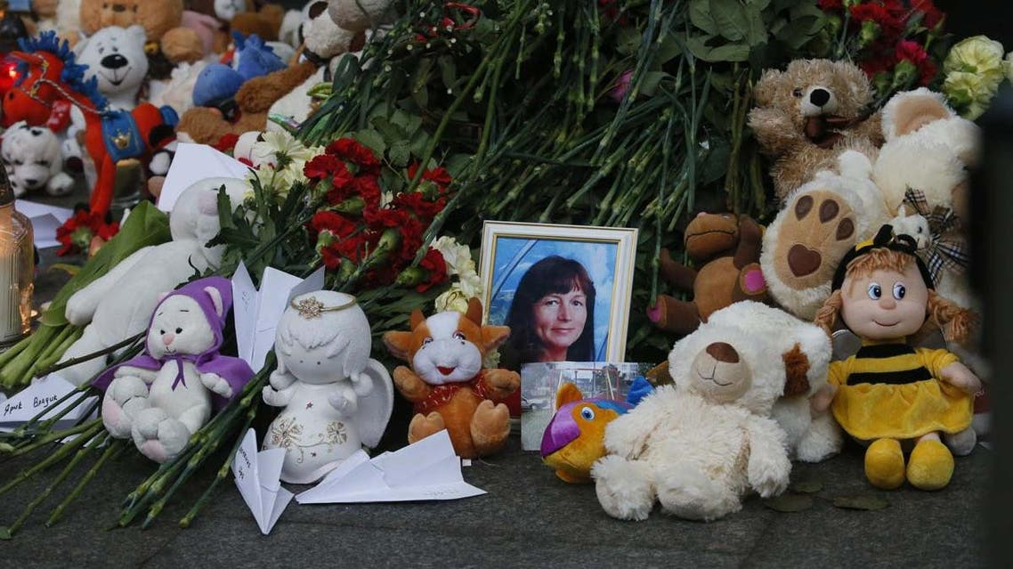 Portraits of plane crash victims are placed near flowers and toys at an entrance of Pulkovo airport outside St. Petersburg, Russia, Wednesday, Nov. 4, 2015. AP