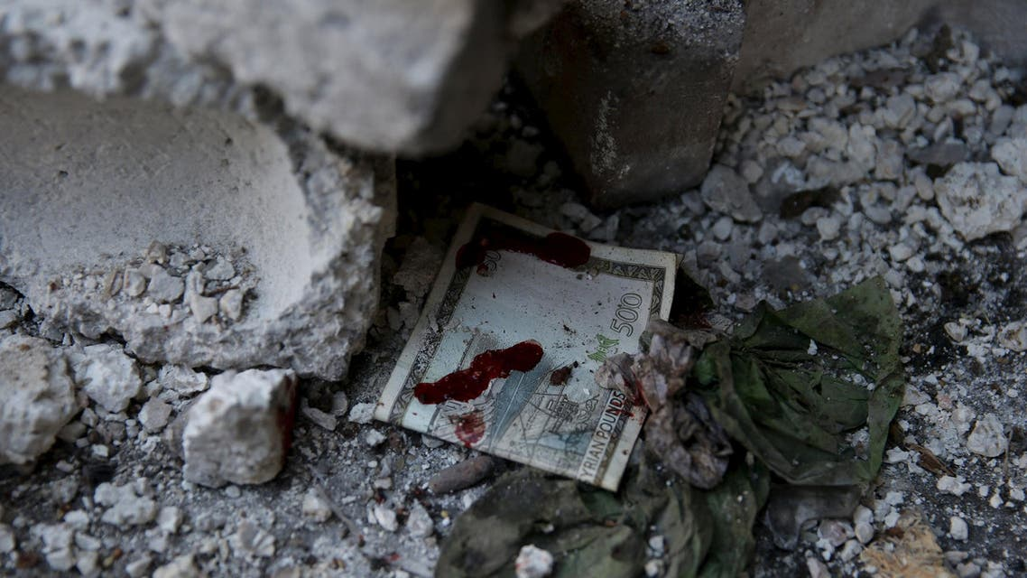 A blood stained Syrian banknote is pictured at a site hit by missiles fired by government forces towards a busy marketplace in the Douma neighborhood of Damascus, Syria October 30, 2015. At least 40 people were killed and about 100 wounded after Syrian government forces fired missiles into the market place in a town near Damascus, a conflict monitor and a local rescue group said on Friday. REUTERS/Bassam Khabieh